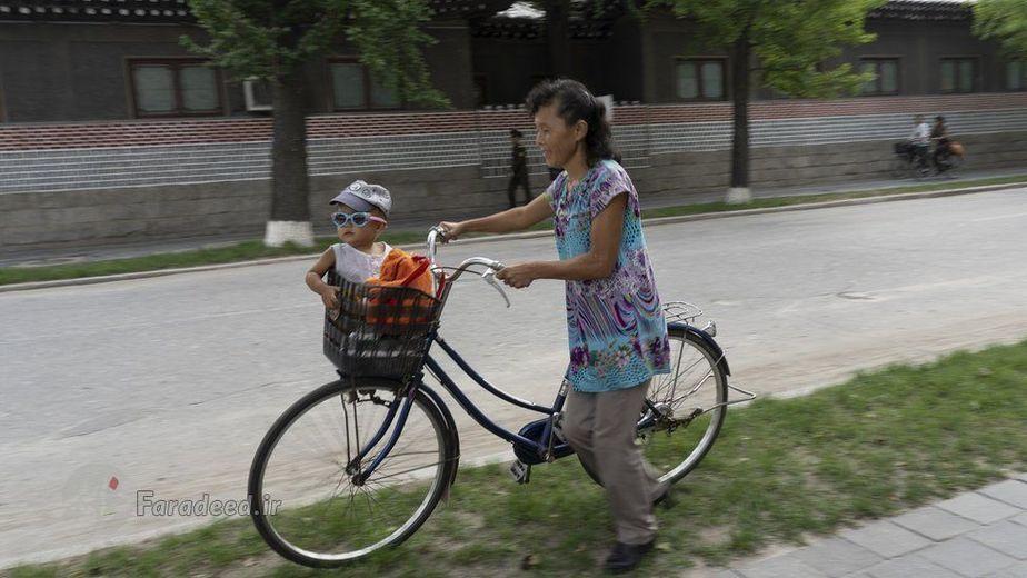 مادری در شهر کائسونگ، به آرامی کودک خود را که در سبد دوچرخه نشانده راه می برد.