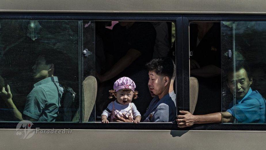 کودکی در آغوش پدرش از پنجره ی اتوبوس بیرون را نگاه می کند.