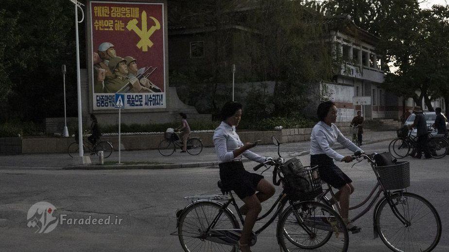 دختری در حال دوچرخه سواری بعد از غروب آفتاب در  Kaesong، موبایلش را هم چک می کند.