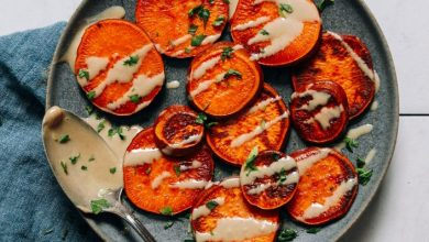 Plate of sliced sweet potatoes drizzled with tahini and parsley